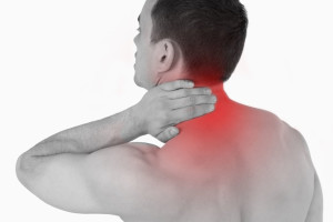 Young man experiencing neck pain against a white background