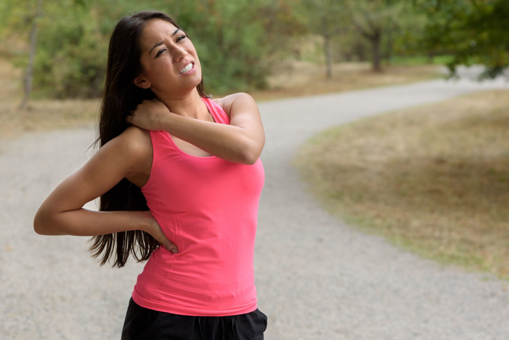 Young woman out jogging suffers a muscle injury